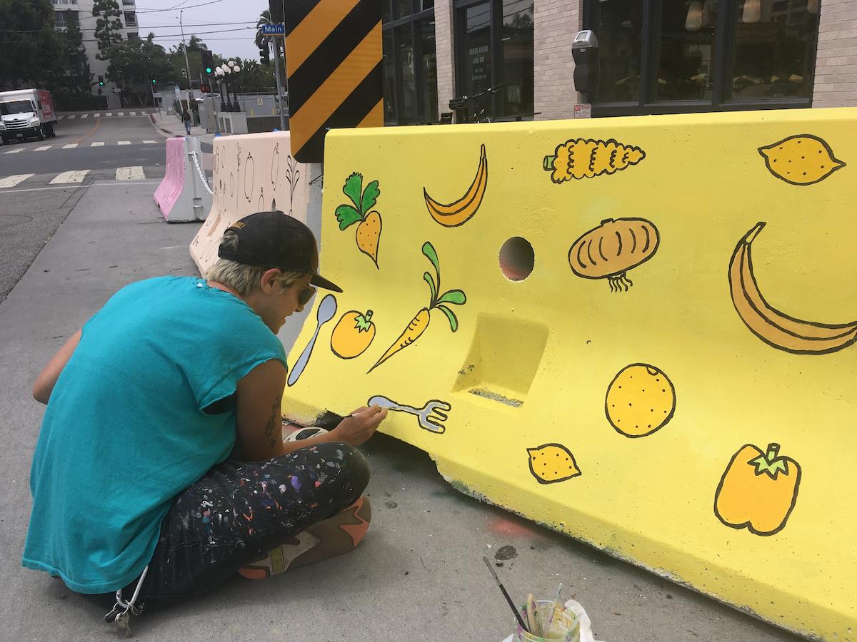 Artist Molly Ellis paints k-rails for Main Street's al fresco dining experience. Photo provided by artist Molly Ellis.